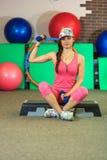 La jeune belle fille blanche dans un costume rose de sports fait des exercices physiques avec des haltères au centre de fitness Photos libres de droits