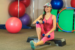 La jeune belle fille blanche dans un costume rose de sports fait des exercices physiques avec des haltères au centre de fitness Images stock