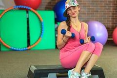 La jeune belle fille blanche dans un costume rose de sports fait des exercices physiques avec des haltères au centre de fitness Photo libre de droits