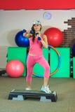 La jeune belle fille blanche dans un costume rose de sports fait des exercices physiques avec des haltères au centre de fitness Image stock