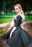 La jeune belle fille blonde avec le rouge à lèvres rouge dans ses grands yeux lumineux et le font dans la robe posant sur les rue Images libres de droits
