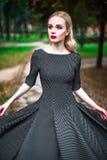 La jeune belle fille blonde avec le rouge à lèvres rouge dans ses grands yeux lumineux et le font dans la robe posant sur les rue Images stock