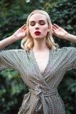 La jeune belle fille blonde avec le rouge à lèvres rouge dans ses grands yeux lumineux et le font dans le costume posant sur le f Photo stock