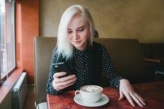 La jeune belle fille blonde examine le téléphone se reposant dans un café Café avec des guimauves pour le petit déjeuner photo libre de droits