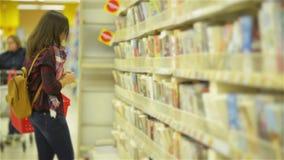 La jeune belle fille choisit un livre dans le supermarché tenant le panier rouge Jolie femme avec des verres presque se tenant clips vidéos