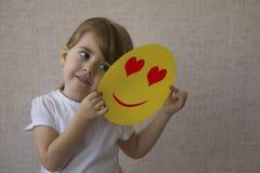 La jeune belle fille dans la chemise blanche sourit et tient dans des ses mains un papier jaune avec un coeur d'aspiration Avec a Photographie stock libre de droits