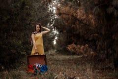 La jeune belle fille dans la forêt pose avec une rétro valise dans des ses mains images libres de droits