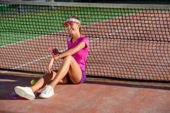 La jeune belle fille dans l'uniforme rose et le chapeau sportif s'assied sur un court de tennis près du filet et utilise le télép image libre de droits