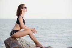 La jeune belle fille dans le bikini s'assied sur la mer proche en pierre avec la bouteille de l'eau Photo stock