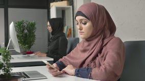 La jeune belle fille dans le hijab rose s'assied dans le bureau et utilise le smartphone Fille dans le hijab noir à l'arrière-pla clips vidéos