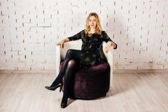 La jeune belle fille dans un plan rapproché de robe égalisante s'assied sur une chaise dans la perspective d'un mur de briques bl photographie stock libre de droits