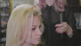La jeune belle fille de coiffeur ajoutent la coiffure de volume au client assez féminin banque de vidéos