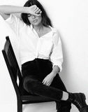 La jeune belle fille de hippie s'asseyant sur la chaise a fatigué dans le shi blanc images stock