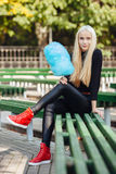 La jeune belle fille de l'adolescence blonde sportive élégante avec la séance cyan-bleue de sucrerie-soie a croisé des jambes au  Photos libres de droits