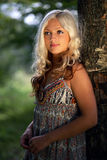 La jeune belle fille fair-haired coûte à un arbre Images libres de droits