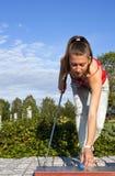 La jeune belle fille joue au golf un jour ensoleillé Photo stock