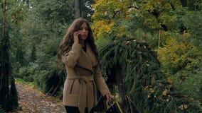 La jeune belle fille marche parc et en parlant au téléphone banque de vidéos