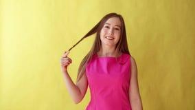 La jeune belle fille montre le prochain geste, flirt, concept de communication, fond jaune banque de vidéos