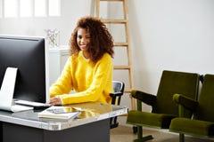 La jeune belle fille noire travaille dans le siège social Image stock