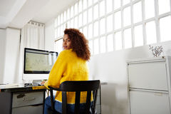 La jeune belle fille noire travaille dans le siège social images stock