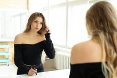 La jeune belle fille peint des yeux et des cils près d'un miroir photos stock