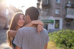 La jeune belle fille regarde le garçon étreignant le sien et le sourire image libre de droits