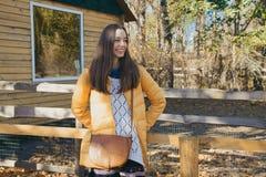 La jeune belle fille se tient près de la barrière en bois dans le zoo de ville Image stock