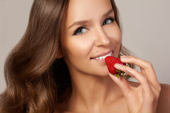 La jeune belle fille avec les cheveux bouclés foncés, les épaules nues et le cou, tenant la fraise pour apprécier le goût et Images libres de droits