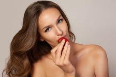 La jeune belle fille avec les cheveux bouclés foncés, les épaules nues et le cou, tenant la fraise pour apprécier le goût et Photo stock