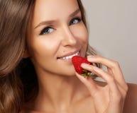 La jeune belle fille avec les cheveux bouclés foncés, les épaules nues et le cou, tenant la fraise pour apprécier le goût et Photos stock