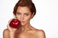 La jeune belle fille avec les cheveux bouclés foncés, les épaules nues et le cou, tenant la grande pomme rouge pour apprécie Photographie stock libre de droits