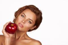 La jeune belle fille avec les cheveux bouclés foncés, les épaules nues et le cou, tenant la grande pomme rouge pour apprécie Images stock