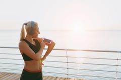 La jeune belle fille sportive avec de longs cheveux blonds dans des écouteurs regarde le téléphone portable le lever de soleil au Photographie stock