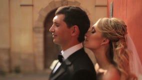La jeune belle jeune mariée blonde touche doucement le sideview du cou de son fiancé Moment très tendre banque de vidéos