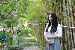 La jeune belle jeunesse adorable mignonne heureuse chinoise asiatique d'étudiant a lu le livre en été d'école de jardin de parc photographie stock libre de droits