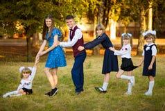 La jeune belle mère mène cinq enfants à l'école Mère de beaucoup d'enfants Famille nombreuse heureux ensemble photos libres de droits