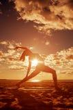 La jeune belle silhouette mince de femme pratique le yoga sur le beac photos stock