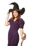 La jeune belle sorcière avec un balai et un chapeau Images stock