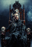 La jeune belle sorcière s'assied sur une chaise Lumineux composez, crâne, thème de Halloween de fumée photos stock