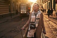 La jeune belle touriste blonde de femme avec une caméra à roues de film de sac et de cru de voyage arrive à une nouvelle ville su photographie stock libre de droits