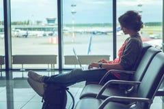 La jeune belle voyageuse de femme s'assied à l'aéroport avec un ordinateur portable Photo libre de droits