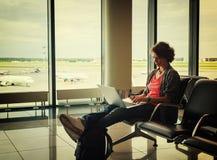 La jeune belle voyageuse de femme s'assied à l'aéroport avec un ordinateur portable Photos stock
