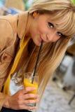 La jeune blonde boit du jus par une paille Images stock