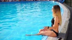 La jeune blonde mince s'assied près d'une piscine, mettant ses jambes dans une eau banque de vidéos