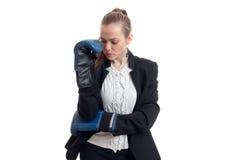 La jeune blonde sexy dans une veste noire et des gants de boxe garde votre main près du visage et a abaissé ses yeux vers le bas Photos libres de droits