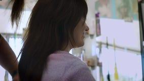 La jeune brune dans le salon fait ses cheveux closeup banque de vidéos