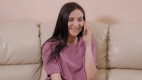 La jeune brune se repose sur le sofa en cuir à la maison et parlant au téléphone banque de vidéos
