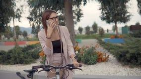 La jeune citadine parle par l'extérieur mobile, tenant la bicyclette banque de vidéos