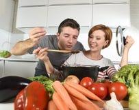 La jeune cuisine attrayante de couples à la maison avec le ragoût végétal d'échantillon de l'homme a fait cuire par son sourire d Images stock