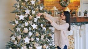 La jeune dame de sourire décore l'arbre de Noël avec des boules, des étoiles et des lumières touchant des décorations et apprécie clips vidéos